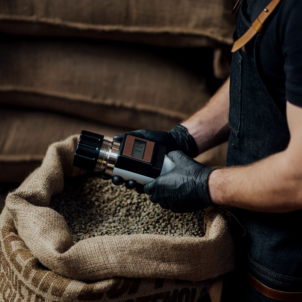 man measuring coffee beans humidity with a special electronic te